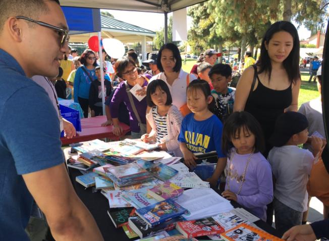 在羅蘭岡馬車節上,公共圖書館捐出200多本圖書,讓孩子們轉輪盤免費索取。(記者楊青/攝影)