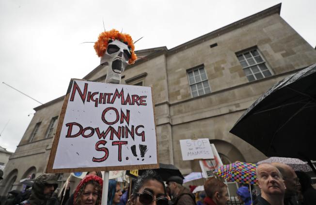 不滿強生首相的英國人舉著標語說,「唐寧街(首相官邸)的夢魘」。(美聯社)