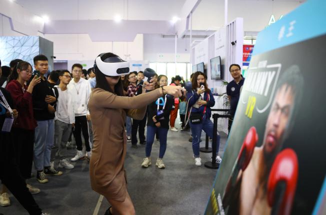 2019世界VR產業大會19日至21日在江西南昌舉行,圖為20日觀眾頭戴VR設備體驗「VR拳擊」,感受真實的拳擊比賽。(中新社)