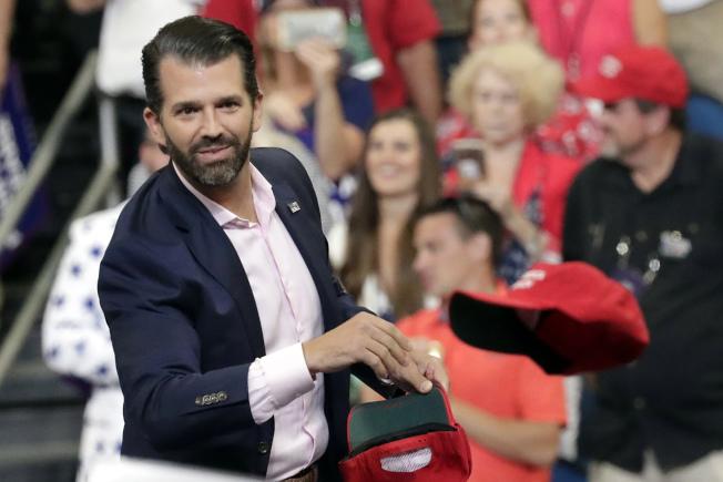 川普總統的長子小唐納,今年6月18日在奧蘭多一場川普造勢活動上,把一頂帽子丟給支持者。(美聯社)