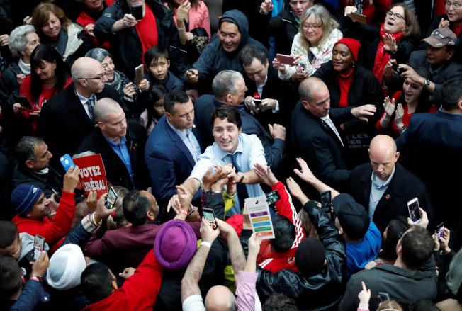 加拿大21日大選,總理杜魯多(中)在最後關頭,全力發動猛攻搶票。他領導的自由黨雖被看好能搶下最多席位,但不足以組成多數黨政府,須仰賴小黨支持。(路透)