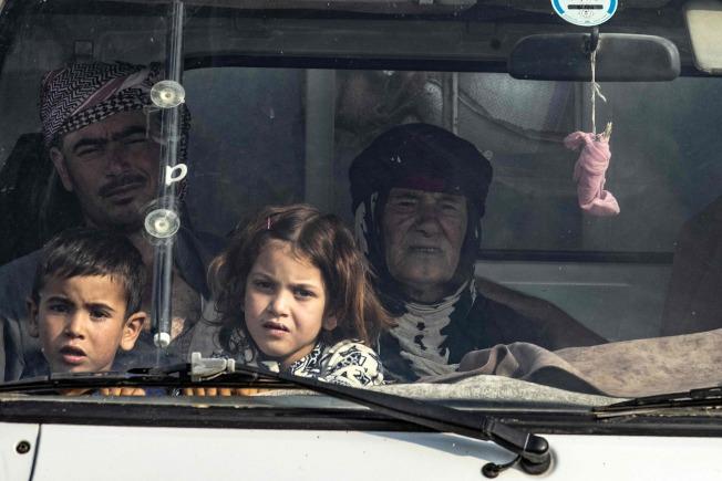 因為停火協議開始,在敘北的庫德族人急忙趁機逃往敘南或其他地區,以免遭到土國部隊殺害。圖為庫德族人帶著孩子19日乘車逃難。(Getty Images)
