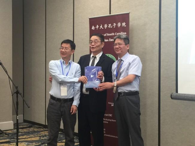 陳旭光(右)與范志忠(左)兩位教授贈送藍皮書給葉坦教授。(記者林麗雪/攝影)