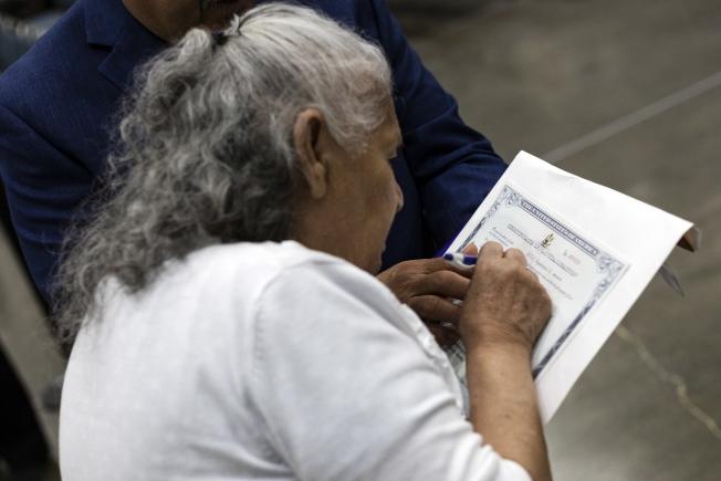 新公民在公民證書上簽字。(歐新社)