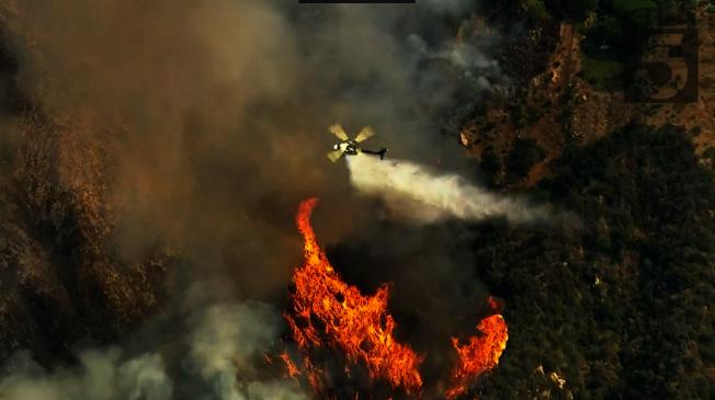 消防員從空中噴撒阻燃劑。   (取自KTLA)