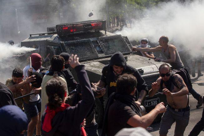智利民眾不滿政府調漲公共運輸票價,廿日在聖地牙哥街頭抗議,並試圖破壞警方的裝甲車。(Getty Images)