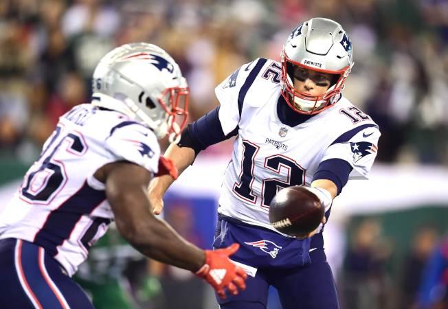 布雷迪(右)將球傳給米切爾。(Getty Images)