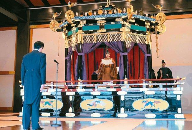 日皇德仁(中)22日在登基儀式發表談話,首相安倍晉三(左)專注聆聽。 (Getty Images)