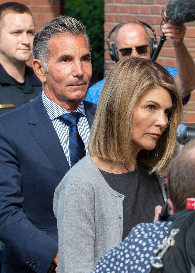 大學錄取弊案出現新進展,好萊塢女星蘿瑞羅夫林(前)和她的丈夫吉安諾里(羅夫林身後)及另外九名家長,22日被追加新控罪。(Getty Images)