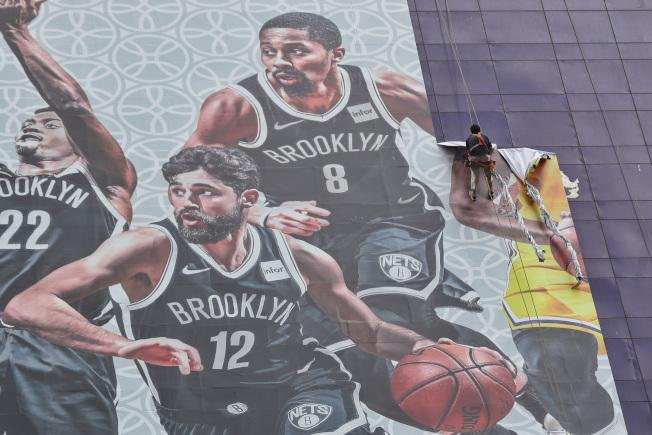 央視確定不轉播23日的NBA開幕戰,圖為日前「2019NBA中國賽」記者會取消時,工作人員將會場外的NBA巨型海報撤下。(中新社)