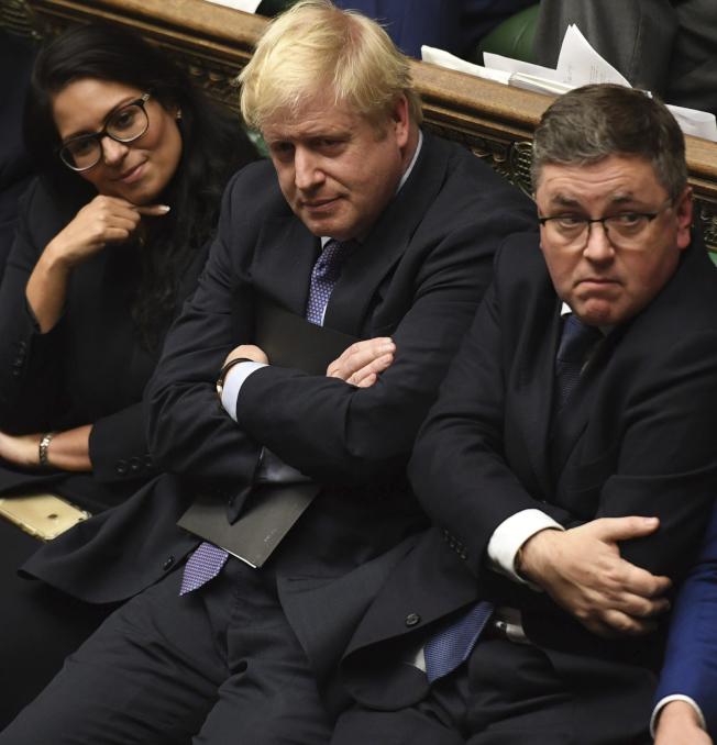 英國議會22日下午否決首相強生的脫歐快速方案。圖為強生(中)在下議院無奈地看著表決結果。(美聯社)