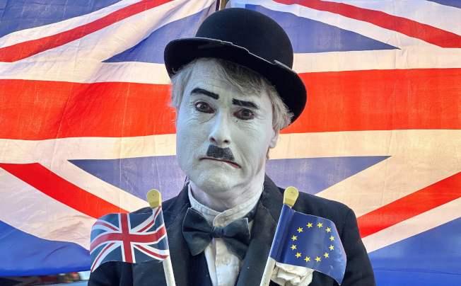 英國上下為脫歐與否,爭議多月,仍無結束。圖為一名英人打扮成默劇諧星卓別林,手持英國與歐盟旗幟,一幅兩難模樣。(Getty Images)