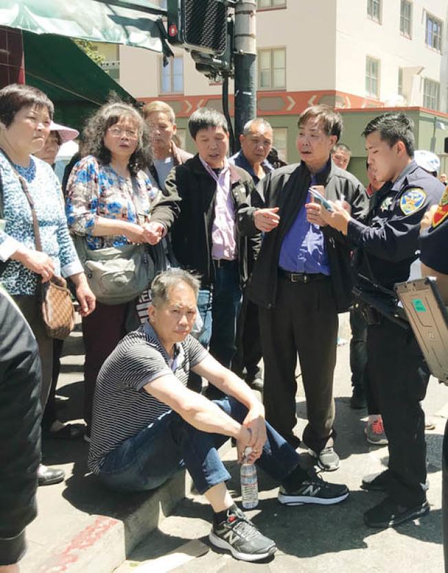 7月15日黃氏宗親總會主席黃中華(坐地者)及中華總會館通事中文書記黃宏昶(右二)在華埠士德頓街被搶劫及毆打受傷。(本報檔案照片,記者李秀蘭攝影)