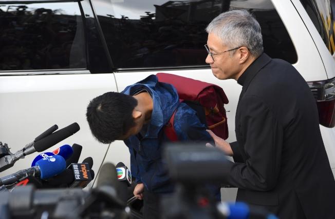 10月23日上午九時,涉及台灣殺人案的疑犯陳同佳(藍色風衣者)當日刑滿於香港壁屋監獄獲釋。圖為陳同佳向死者潘曉穎家人鞠躬道歉。(中通社)