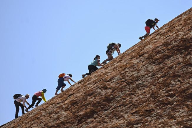 澳洲宣布,將禁止攀登著名的紅色砂岩烏魯魯。圖為最後一批觀光客25日手腳併用向上爬。(美聯社)