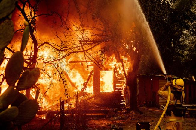 風助火勢,民宅已陷入火海,消防員仍奮勇灌救。(美聯社)
