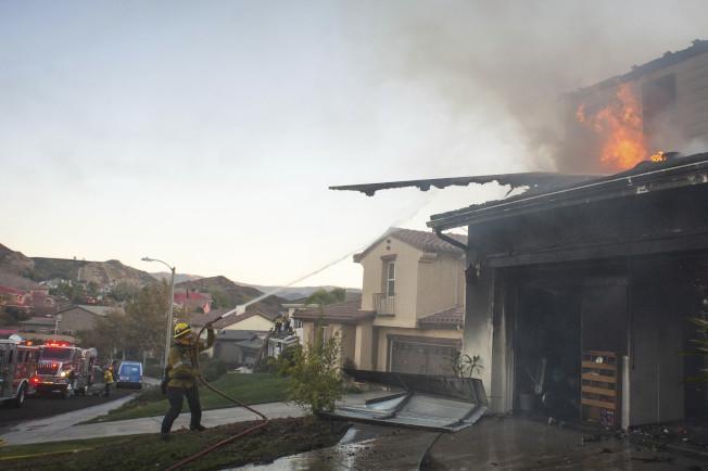 南加州野火逼近洛杉磯縣的居民區,消防員忙著與大火搏鬥。(美聯社)