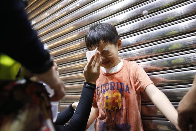 香港27日舉行譴責警察濫權暴力的集會,遭警方以催淚彈、胡椒噴霧強力驅離。圖為一名兒童遭催淚彈熏眼。(歐新社)