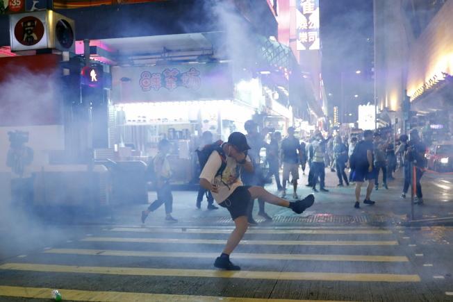 香港示威者網上發起27日多區示威行動,警方出動水炮車和發射催淚彈,一名示威者將催淚瓦斯罐踢回警方。(歐新社)