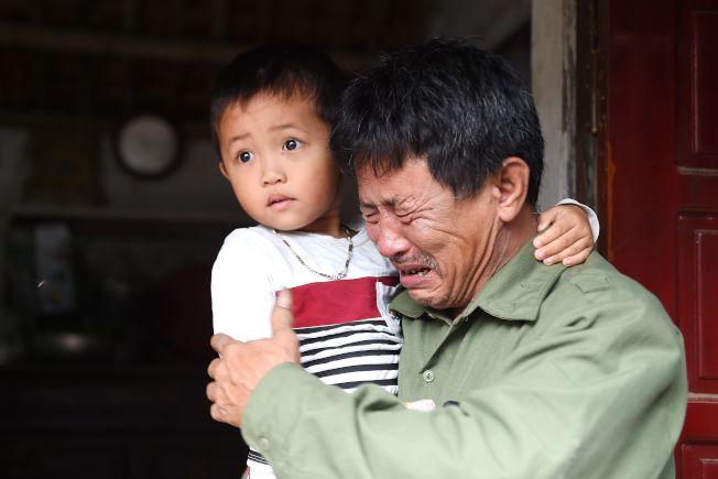 Le Van Ha的父親抱著孫子痛哭。Le Van Ha疑似在英國貨櫃案中喪命。(Getty Images)