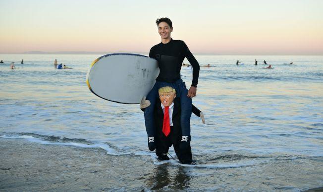 衝浪者Aj Cantu在加州的一場萬聖節衝浪活動Blackies Halloween Surf中,展現一套看起來像是騎在了川普肩膀上的萬聖節服裝。(Getty Images)