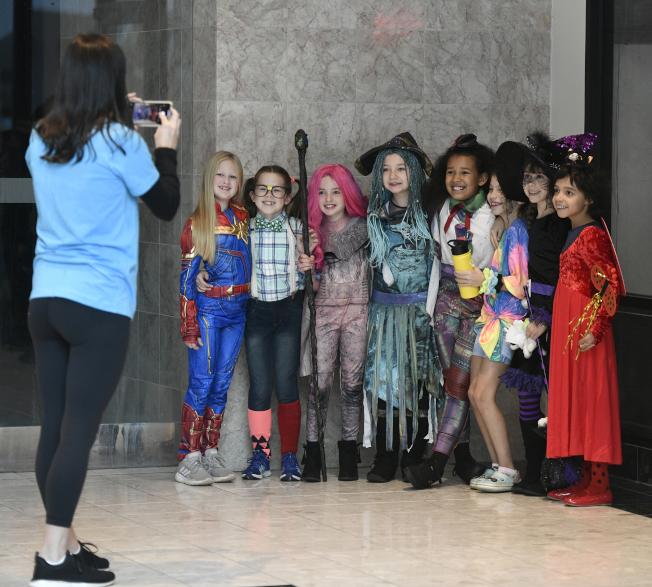 28日,賓州一位教師Carrie Basile給學生拍照。他們正準備去參加一場萬聖節遊行。(美聯社)