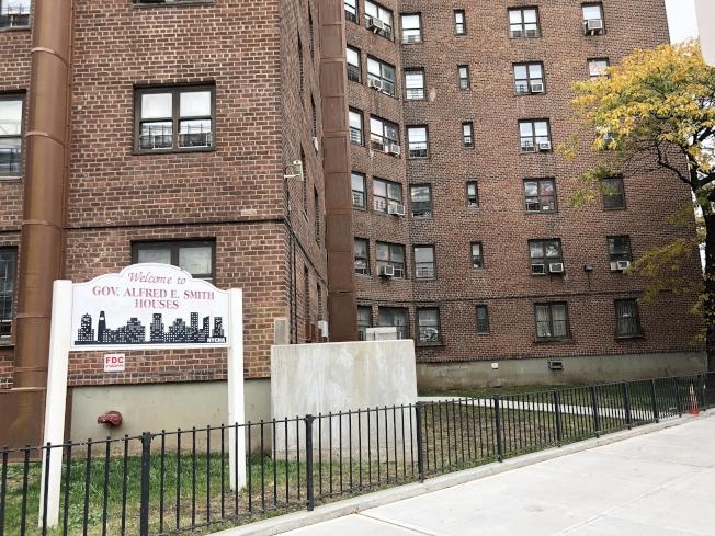 案發位於曼哈頓華埠的史密斯政府樓,墜樓地就在標識牌後方的草地。(記者張晨/攝影)