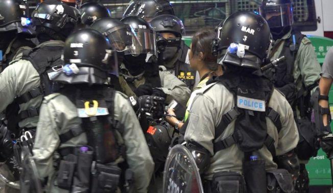 網媒《HKFP》自由攝影記者May James(中),周日在旺角採訪期間被警員截查,她與警員理論後,涉阻差辦公被捕。(記協提供)