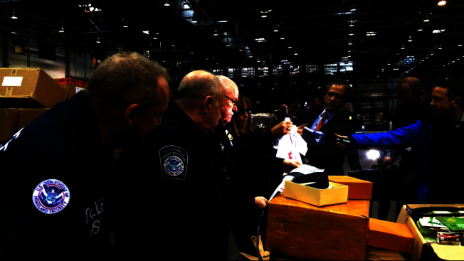 CBP執法人員在甘迺迪機場開箱檢查仿冒品,以貨品的價格、質量等驗證是否為仿冒品。(記者牟蘭/攝影)