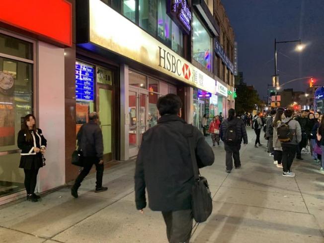 夜幕降臨,華裔按摩女在法拉盛緬街街頭分發小廣告。(記者牟蘭/攝影)