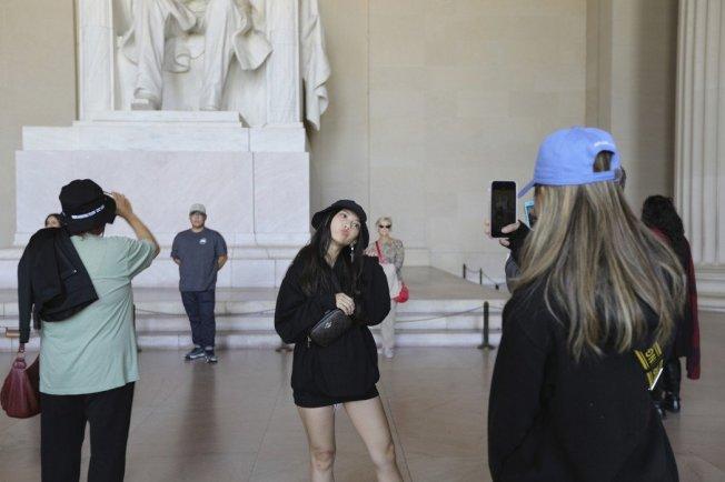 受美中貿易戰影響,赴美觀光的中國遊客明顯減少,圖為在華府林肯紀念堂拍照的觀光客。 (美聯社)