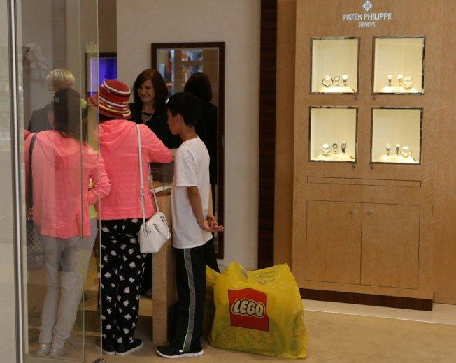 中國觀光客消費實力強,圖為一個中國家庭在加州一間購物中心的精品店購物。 (美聯社)