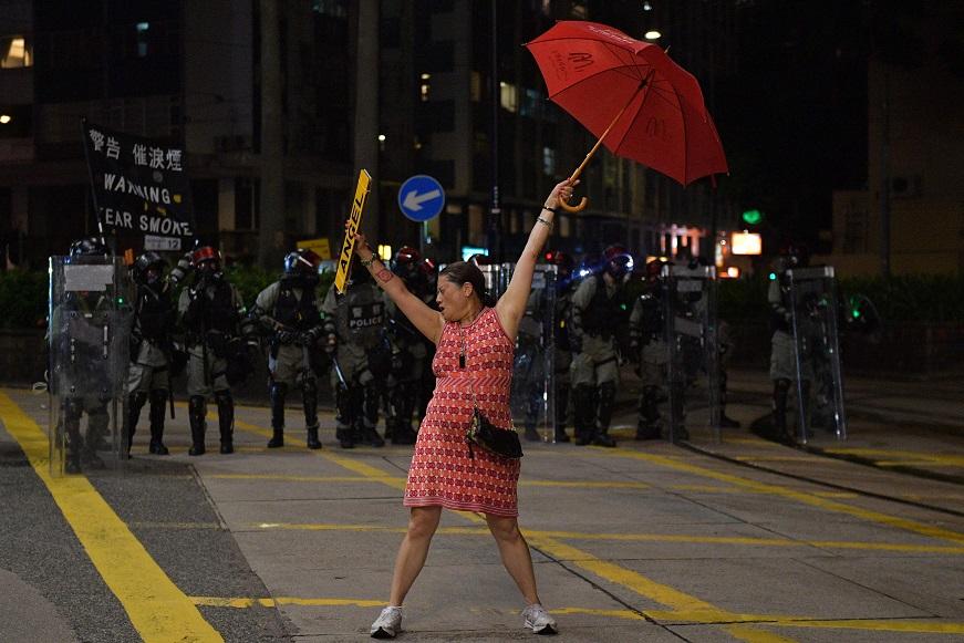 10月1日,一名香港婦女站在港警前,一手持雨傘,一手持一個寫「天使」的車牌。(Getty Images)
