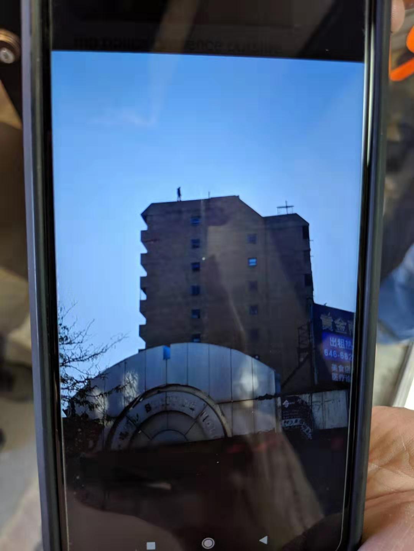 紐約法拉盛一棟大樓,樓上傳有民眾要跳樓 ,警方已趕至現場救援。圖/讀者提供