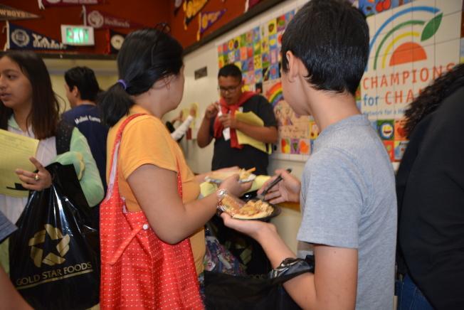 現場學生和家長大飽口福,吃得開心。(記者丁曙/攝影)