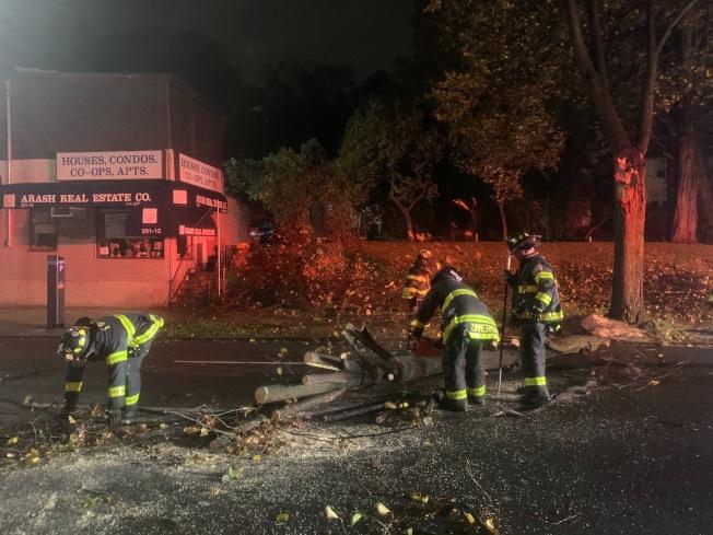 1日凌晨在皇后區小頸251街夾北方大道路口,被狂風吹斷的樹幹攔腰阻斷交通,消防員連夜到場處理。(記者曹健/攝影)