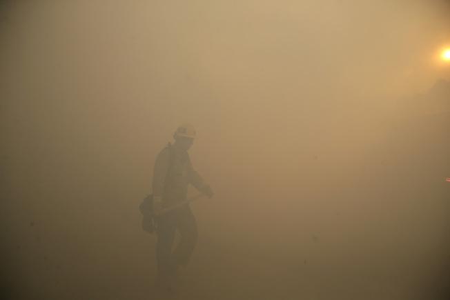 30日,加州洛杉磯縣近郊的西米谷(Simi Valley),消防員在濃煙之中對抗大火。(美聯社)