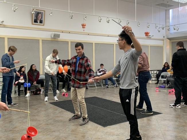 19歲文化老師羅英九(右一)練習扯鈴七年,他以結合音樂的花式扯鈴表演推廣傳統藝術,吸引大批學生體驗。(本報記者/攝影)