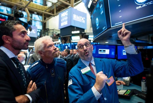 主張向大公司和富豪徵稅的華倫氣勢走高,華爾街感到不安。圖為紐約證交所交易員向維珍航空老闆超級富豪布蘭森講解。(Getty Images)