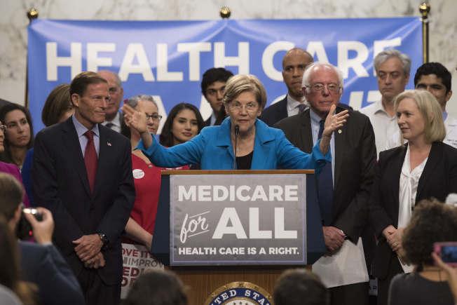 華倫提出全民健保政見,宣稱不會增加中產階級財務負擔,而是向大公司及富豪課稅。圖為華倫在2017年和參議員桑德斯(右前二)介紹她的政策。(Getty Images)