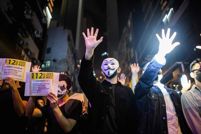 示威者萬聖節晚上拿著「112維園見」標語,呼籲民眾2日上街遊行。(Getty Images)
