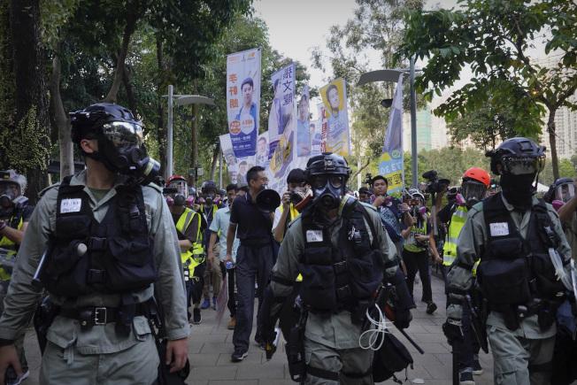 香港鎮暴警察出動,經過一片選舉候選人的旗幟。(美聯社)