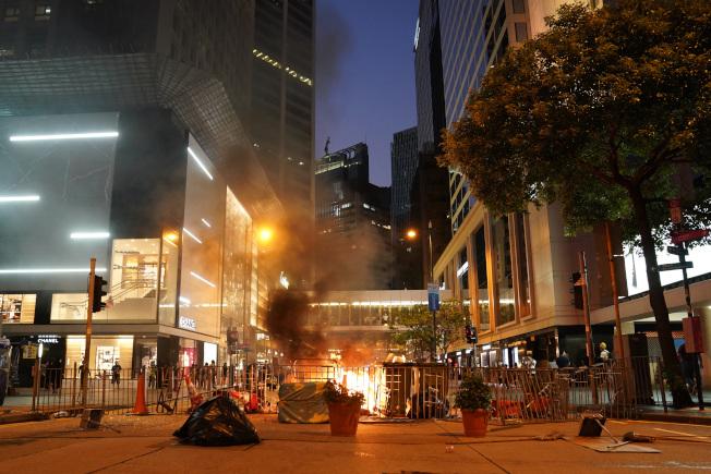 示威者在香港中環鬧區當街焚燒障礙物。(新華社)