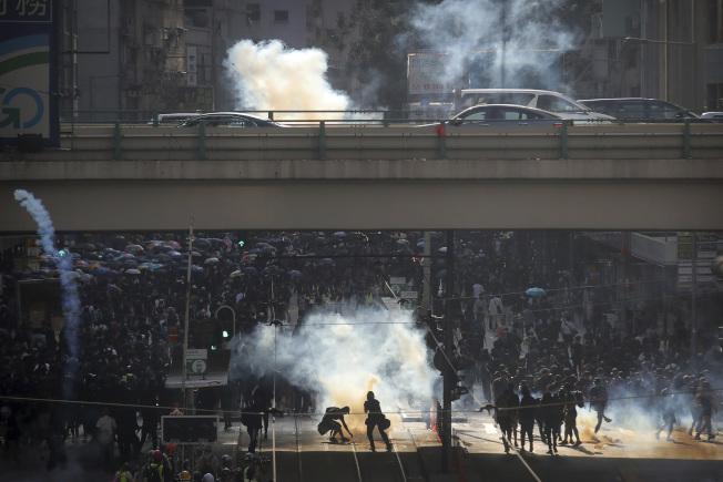 香港示威失控,鎮暴警察發射催淚彈驅散示威者。(美聯社)