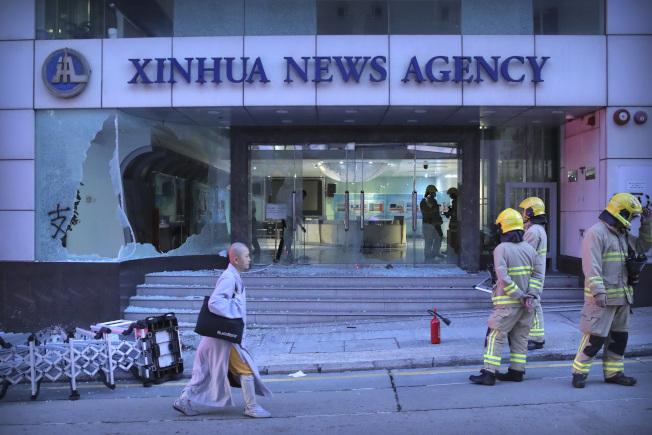 香港示威失控,示威者衝進官方新華社香港分社,砸破玻璃,往裡面投擲自製燃燒彈。圖為火勢撲滅後,香港消防員站在新華社香港分社外面戒備。(美聯社)