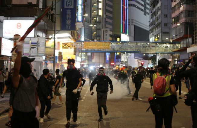 香港示威持續失控,圖為鎮暴警察2日在銅鑼灣鬧區發射催淚彈驅逐示威者。(新華社)