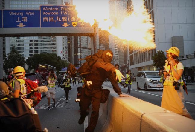 圖為一名示威者投擲自製的燃燒彈。(美聯社)