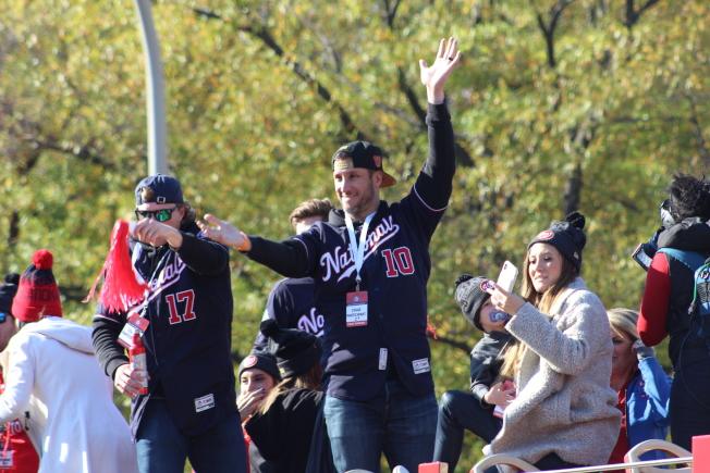 國民隊隊員在遊行巴士上向觀眾揮手。(記者張筠╱攝影)