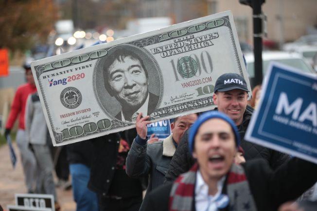 華裔參選人楊安澤在民主黨內力爭上游,支持者拿著巨型鈔票,上面換上他的頭像。(Getty Images)