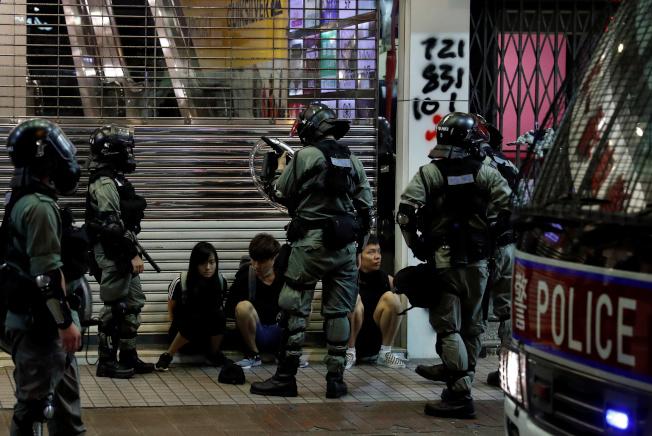 集會示威期間,多位民眾遭警員攔查。(路透)